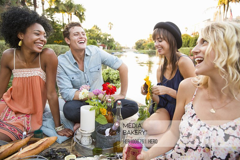 Laughing friends enjoying picnic, drinking wine on raft on summer lake