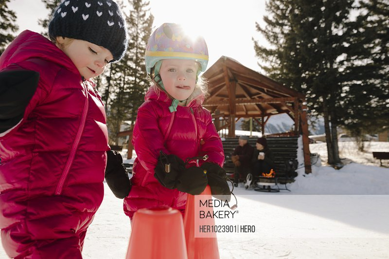 Cute toddler girls playing in snow