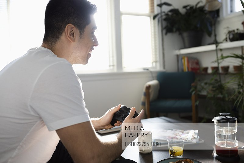 Young Latinx man playing video game in living room