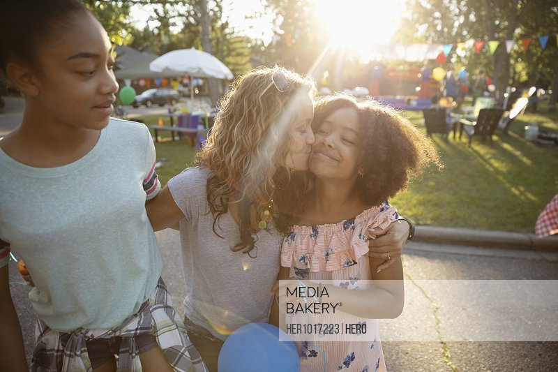 Affectionate mother kissing daughters cheek at summer neighborhood block party in park