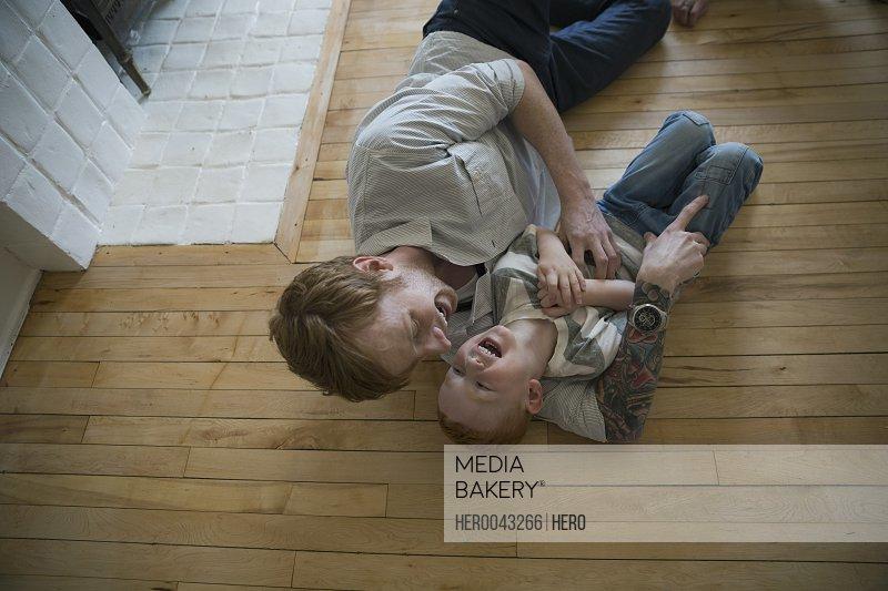 Playful father tickling son on hardwood floor