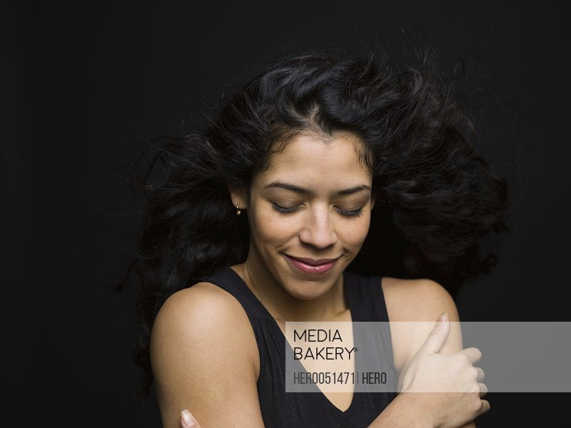 Portrait serene woman with eyes closed and wind blowing long curly black hair against black background