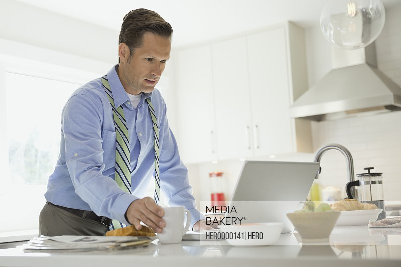 Mature businessman using laptop in domestic kitchen
