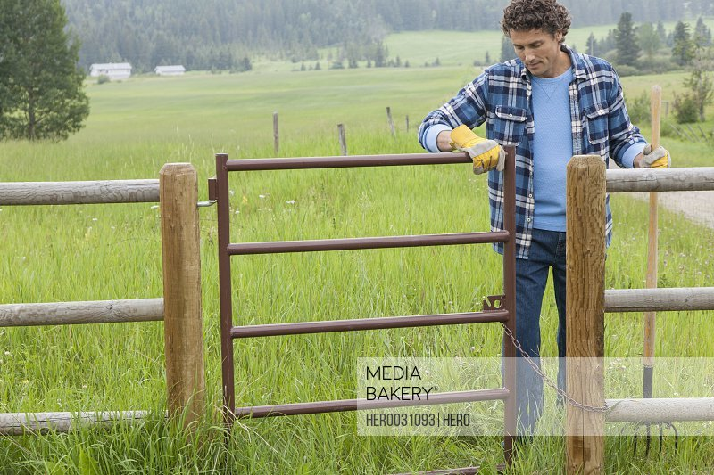 middle aged man opening gate to paddock on rural property