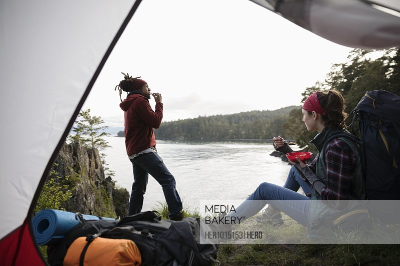 Couple eating, camping on cliff overlooking ocean