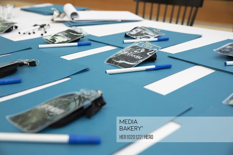 ID badges, folders and pens ready on conference check-in table