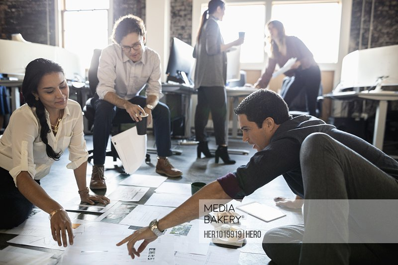 Creative business people reviewing proofs on loft office floor