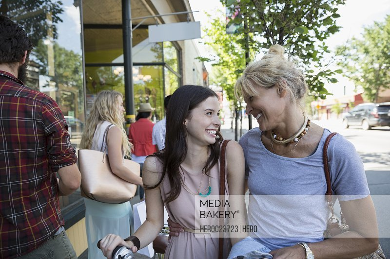 Smiling mother and daughter outside storefront