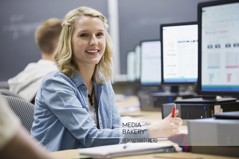 Portrait smiling college student in computer lab classroom