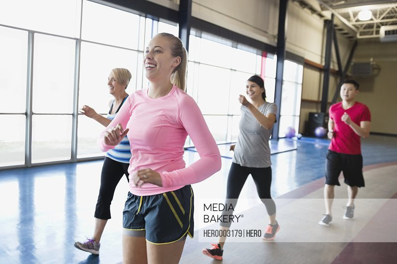 Woman jogging with friends in fitness center