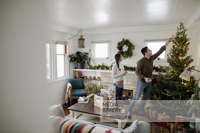 Young couple decorating Christmas tree in living room