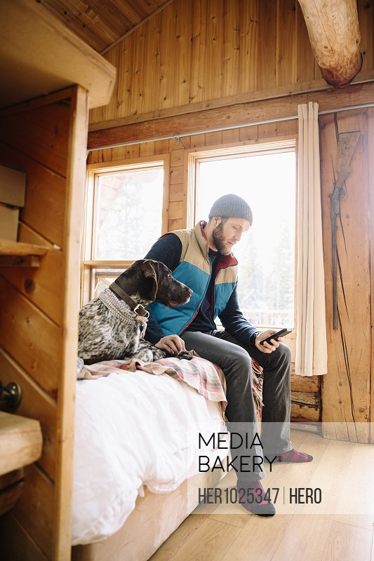 Man with dog using smart phone on cabin bed