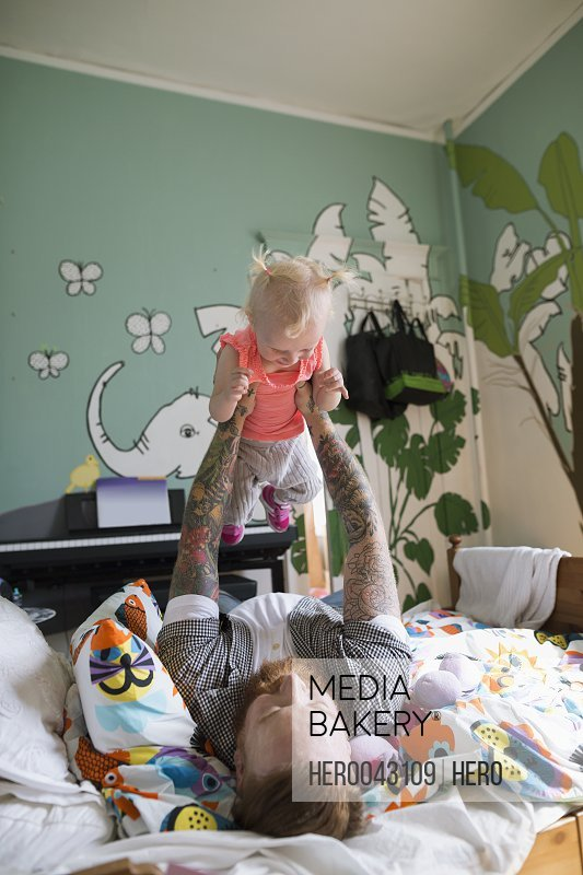 Father holding daughter overhead on bed