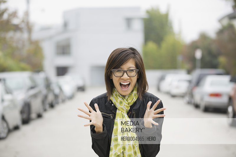 Portrait of excited woman standing on street