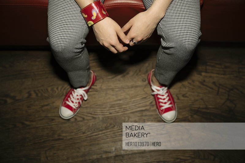 Low section stylish female millennial wearing red sneakers