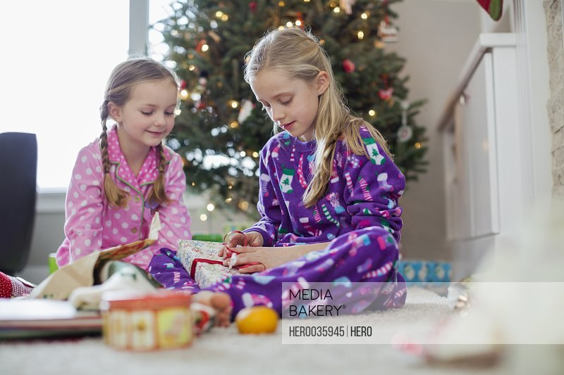 Young girls opening Christmas gifts