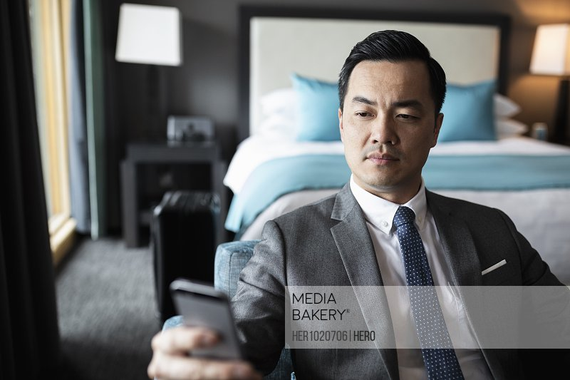 Businessman using smart phone in hotel room