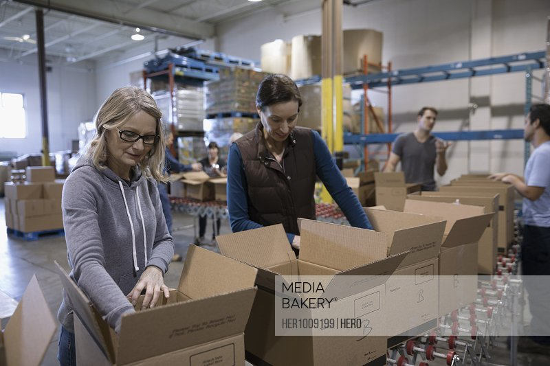 Female volunteers filling boxes for food drive in warehouse