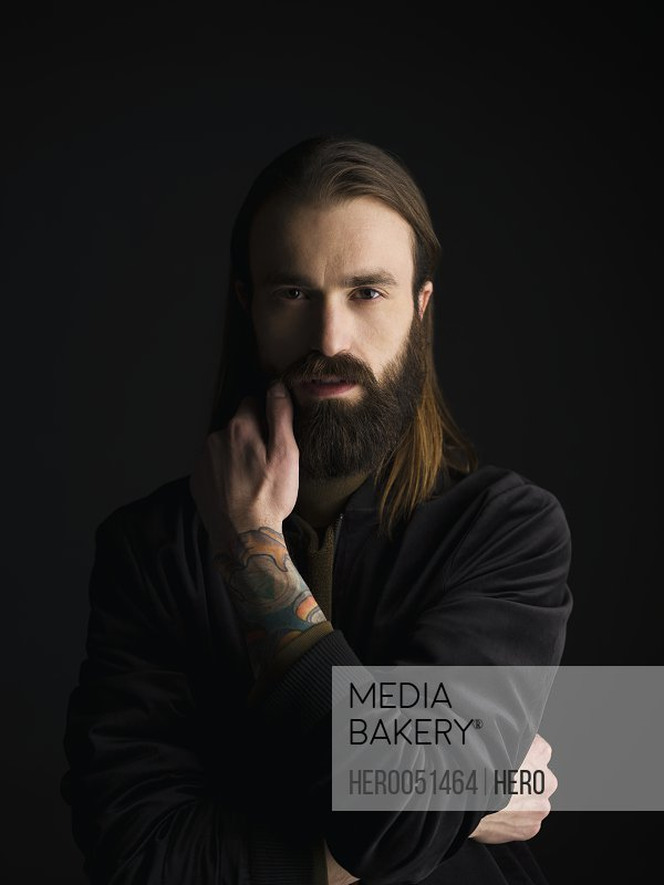 Portrait serious tattooed brunette man with beard against black background