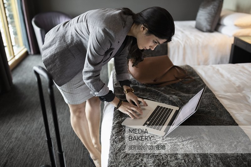 Businesswoman bending over laptop on bed in hotel room