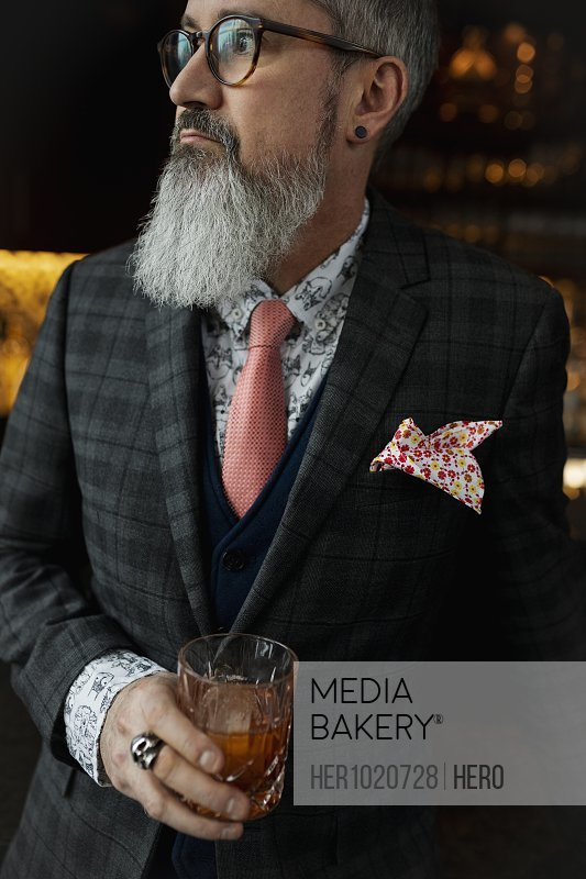 Fashionable hipster businessman with beard drinking cocktail