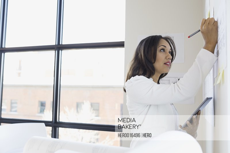 Businesswoman with digital tablet writing at wall