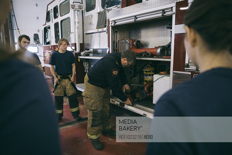 Firefighters meeting, checking equipment at fire engine
