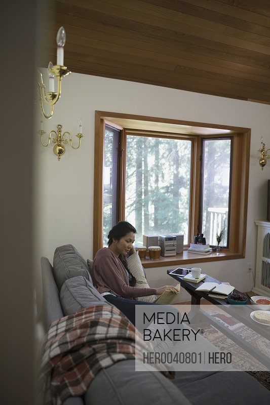 Comfortable woman reading book on cabin sofa