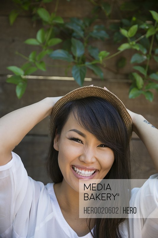 Portrait enthusiastic woman with black hair wearing hat