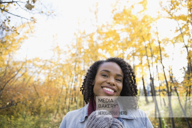 Portrait smiling woman with curly black hair in autumn woods