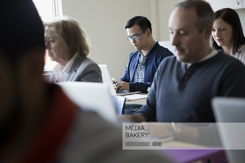 Adult education students using laptops in classroom
