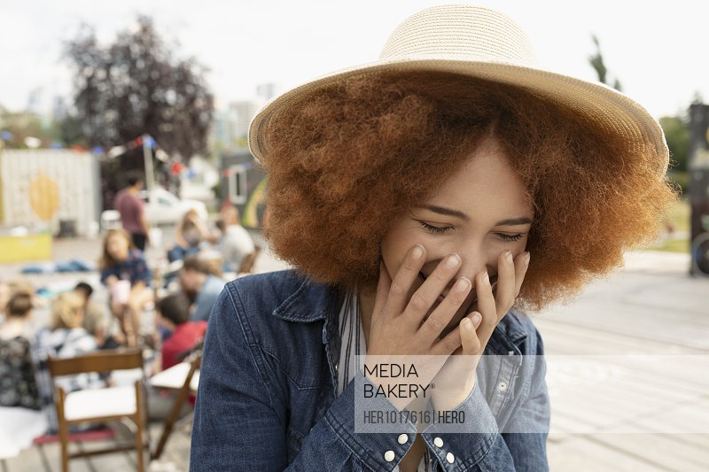 Laughing young woman in urban park