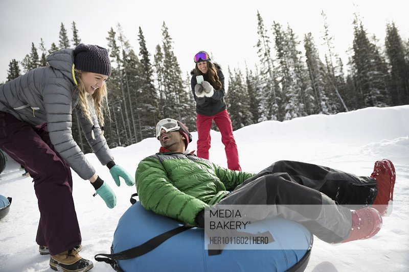 Friends playing, inner tubing in snow