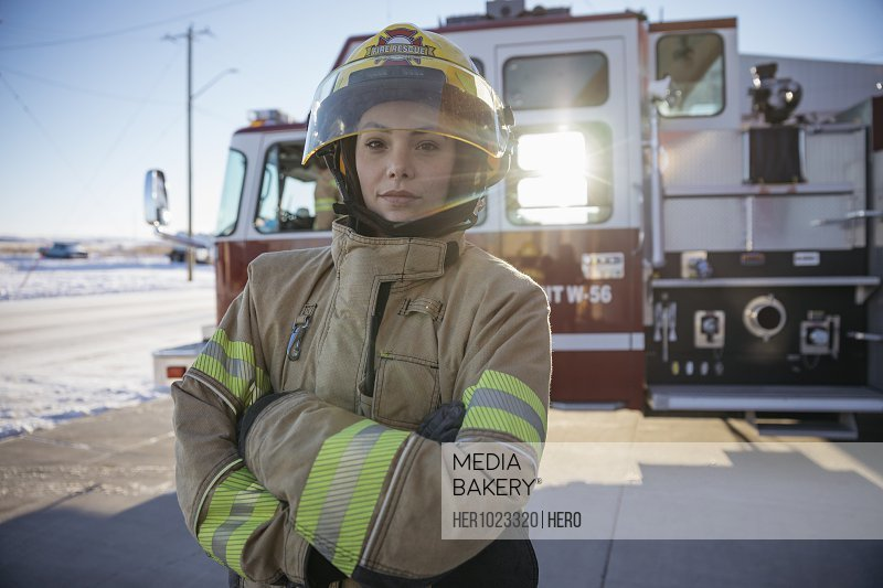 Portrait confident, tough female firefighter standing in front of fire engine