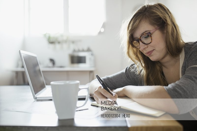 Businesswoman writing in notebook at laptop