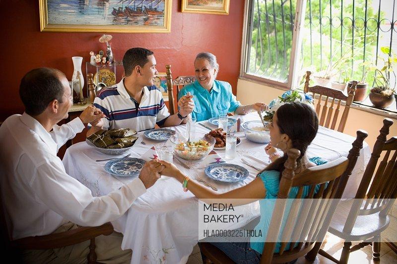 family praying around table - 800×533
