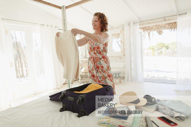 Woman unpacking suitcase in beach hut bedroom