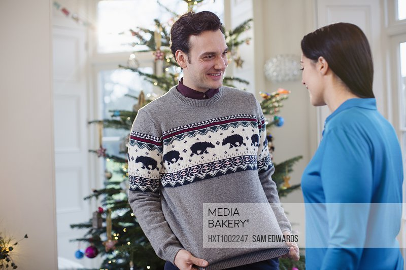 Husband showing Christmas sweater to wife