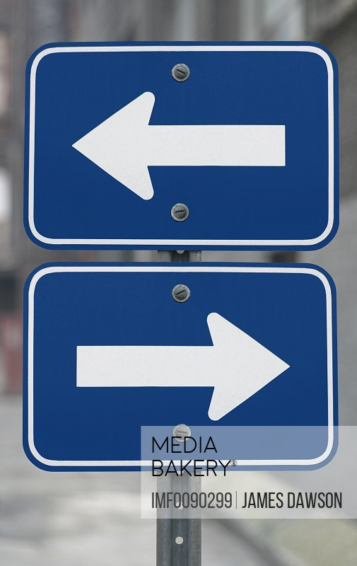 Photo by Image Farm - Two-part blue metal road sign with blank white  directional arrows pointing left and right in opposite directions and with  an