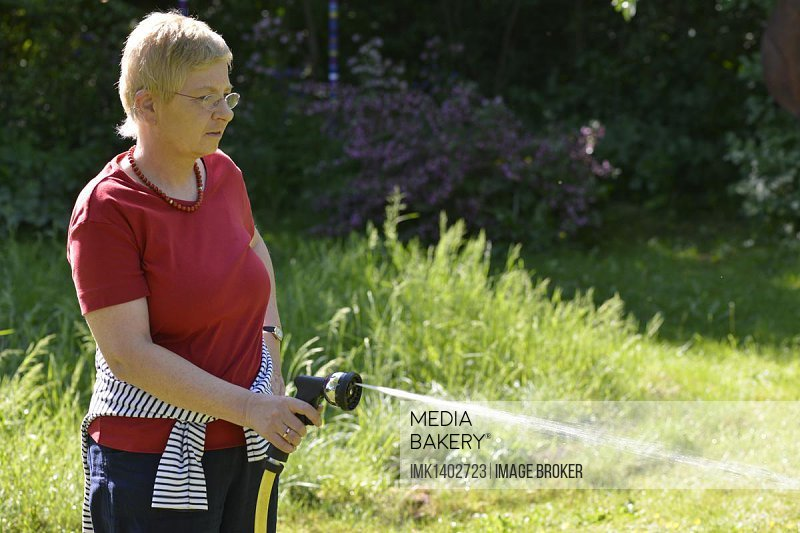 Woman watering the plants in the garden with a hose and a spray gun