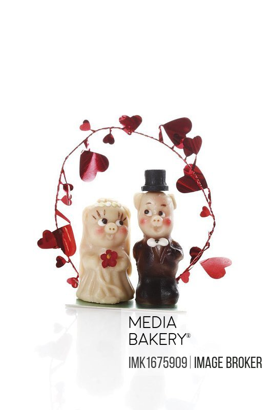Marzipan figurines, marzipan pigs in wedding clothes under an arch with hearts garland