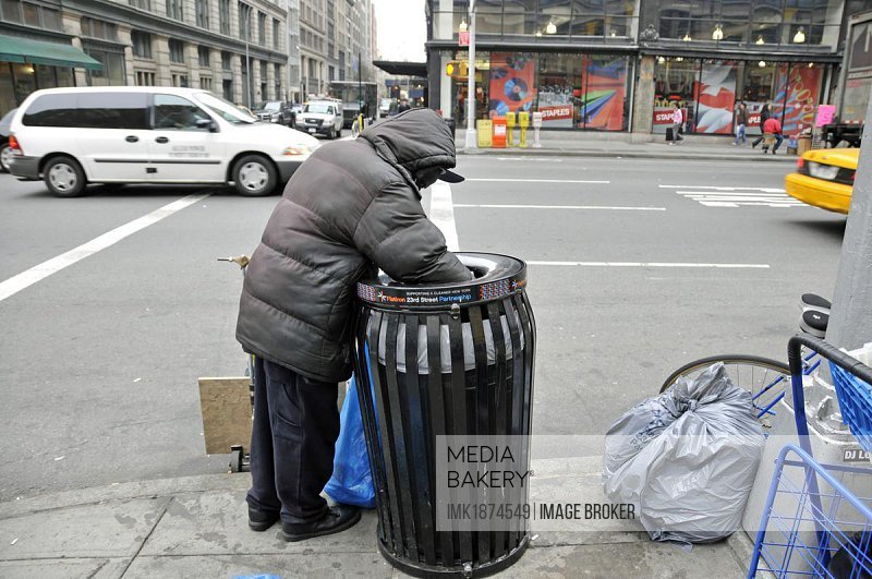 Homeless person rummaging through a trash can, looking for salvageable items, Manhattan, New York City, USA, North America