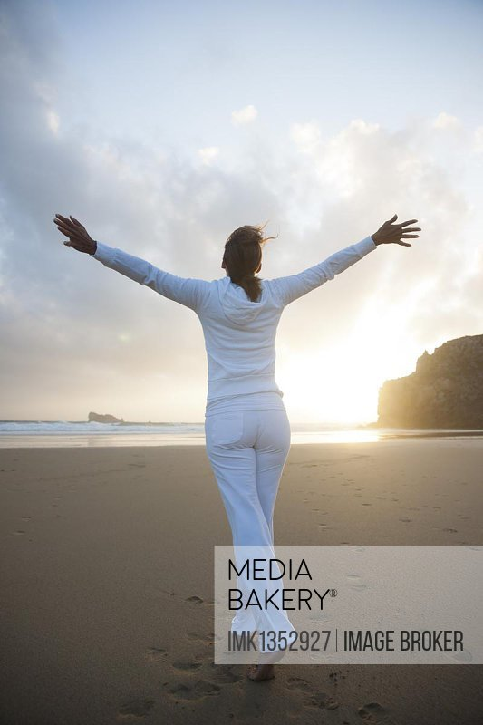 Woman doing relaxation exercises on a beach at sunset