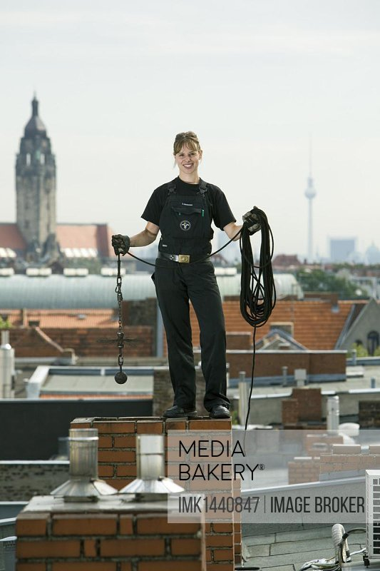 Chimney champion Steffi Marienfeld at work on the roof of a house in Charlottenburg, with the Berlin Television Tower on the horizon, Berlin, Germany, Europe
