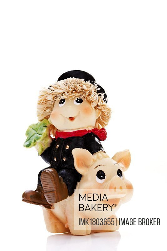 Chimney sweep on top of a pig holding a four-leaved clover, symbols of good luck