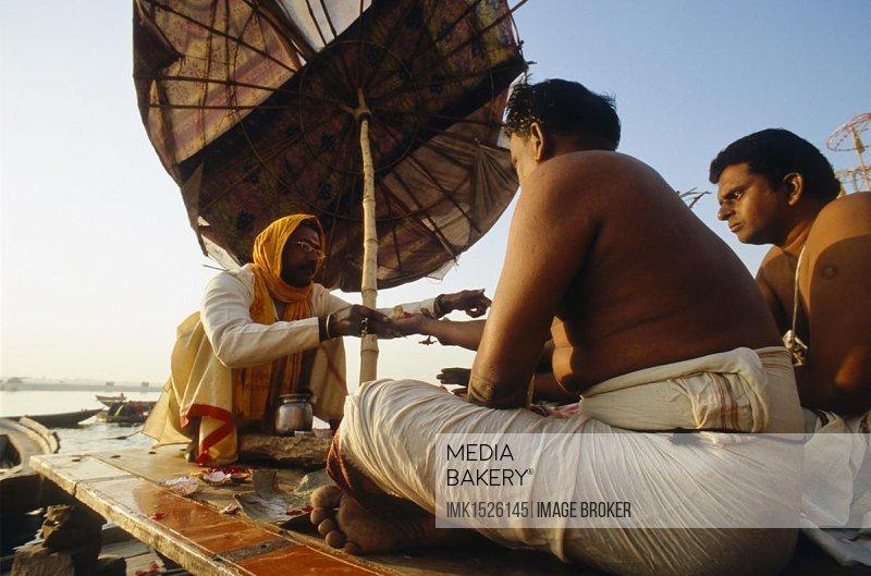 Priest offering ceremonies and blessings to pilgrims, Varanasi, Uttar Pradesh, India, Asia