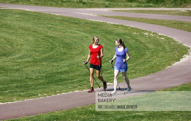 Young women, 25 - 30 years, Nordic walking with walking sticks