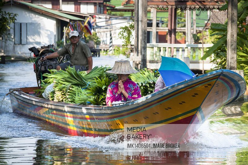 Fully laden boat, woman, Wai, traditional gesture of greeting and paying respect, Khlong or Klong, canal, Bangkok, Thailand, Asia