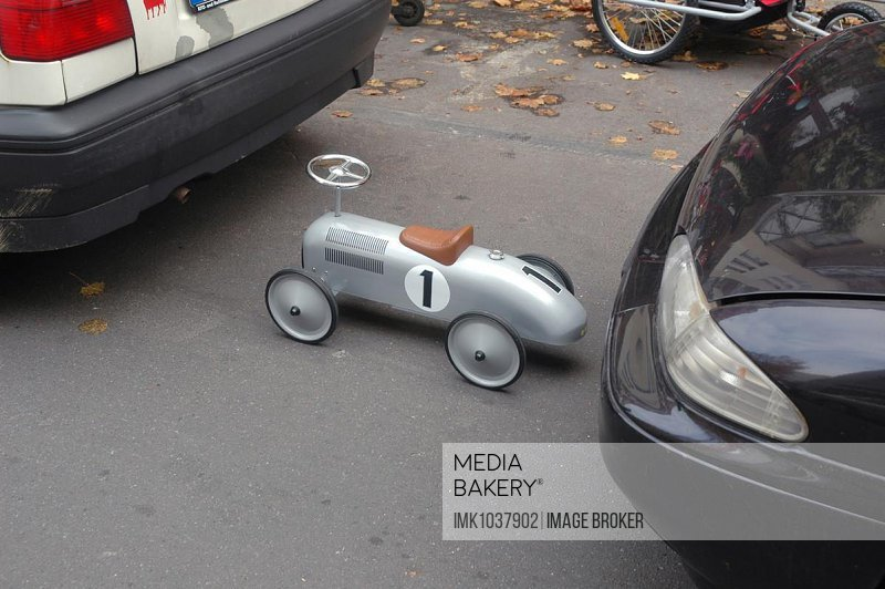 Size difference, small toy car on the parking lot, Berlin, Germany, Europe