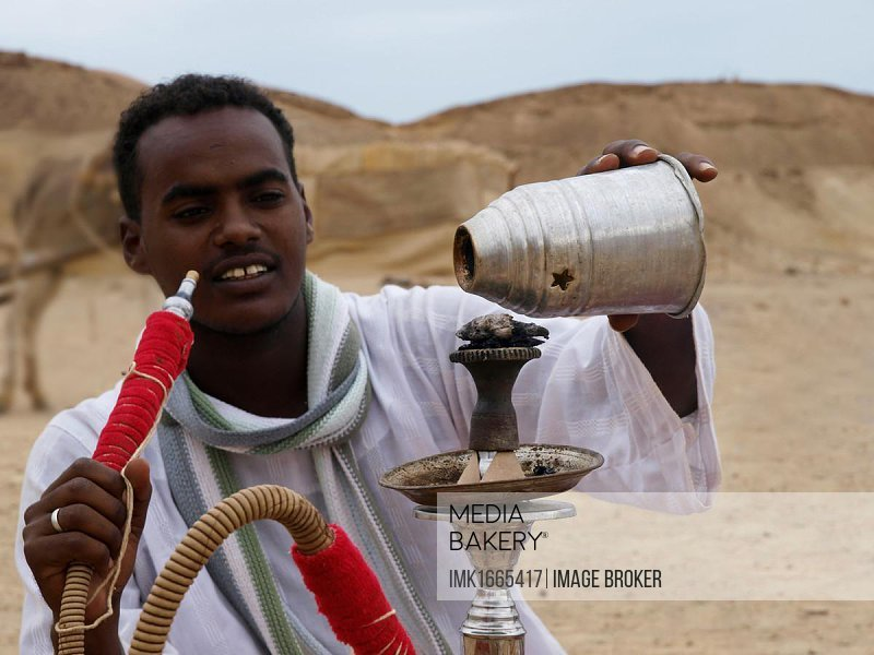 Bedouin preparing a water pipe, desert peoples from Egypt meeting in Wadi el Gamal National Park, Valley of the Camels, for the the Bedouin Cultural Festival, southeast Egypt, Africa